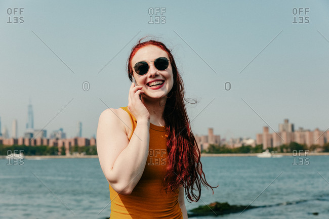 Young woman talking on phone by waterfront.