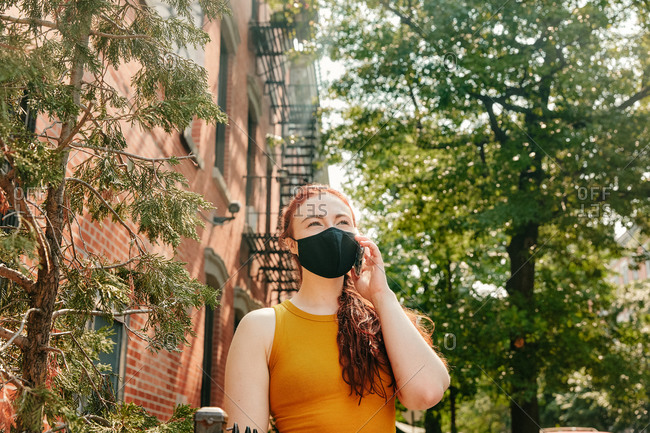 Young woman on phone wearing facemask in brooklyn street by trees.
