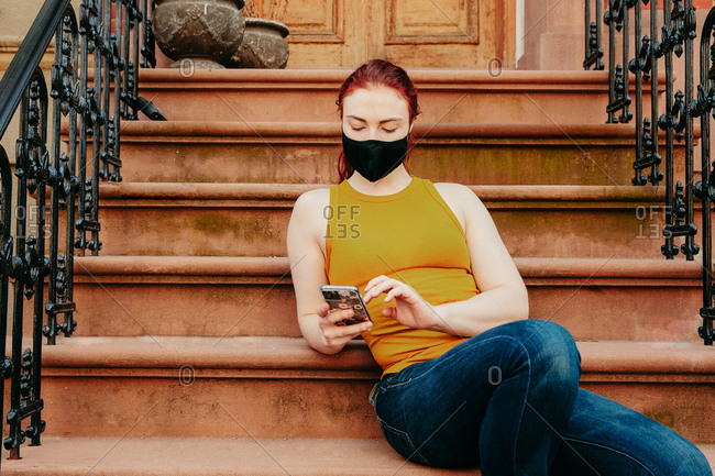 Portrait of a young woman sitting on brooklyn stoop texting on phone.