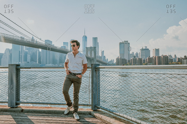 Young man standing by east river.