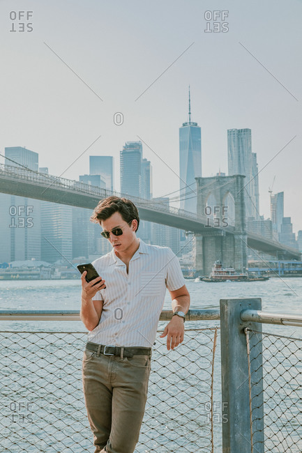 Young man standing by river with phone.