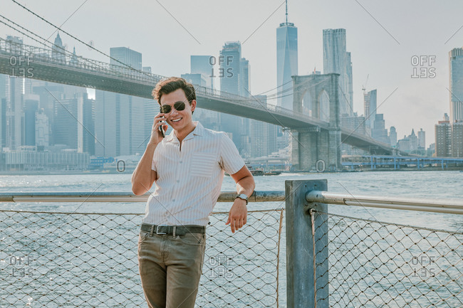 Young man standing by river talking on phone.