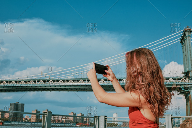 Young woman by river taking picture with phone