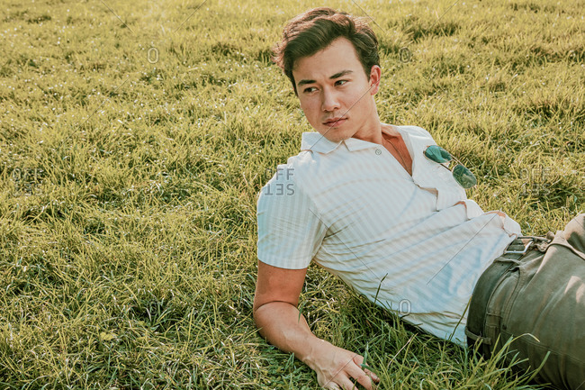 Portrait of a young man sitting on grass.