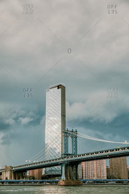 City skyline and manhattan bridge with storm clouds.