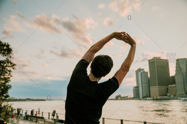 Male athlete stretching on waterfront during sunset.