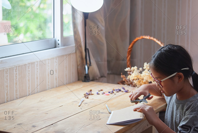 A girl trimming the hand craft book
