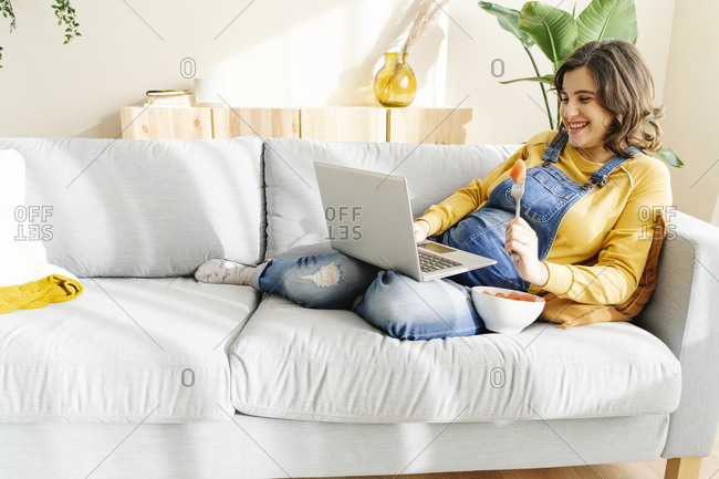 Smiling pregnant young woman working on her laptop and eating fruit on a sofa. work at home concept
