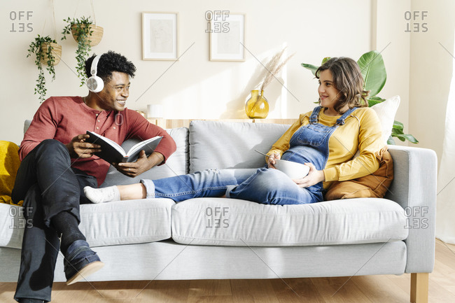 Pregnant wife eating on the couch with her husband who is listening to music and reading a book. interracial couple concept