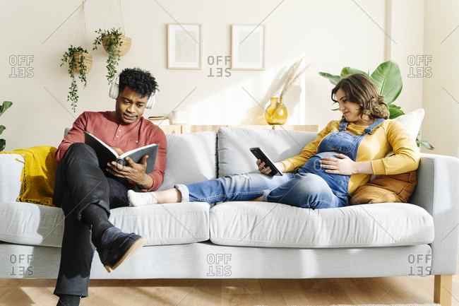 Husband listening to music and reading a book with his pregnant wife who is watching a tablet on a sofa. interracial couple concept