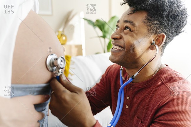 Husband listening to his wife's baby heartbeat with a stethoscope. interracial couple concept