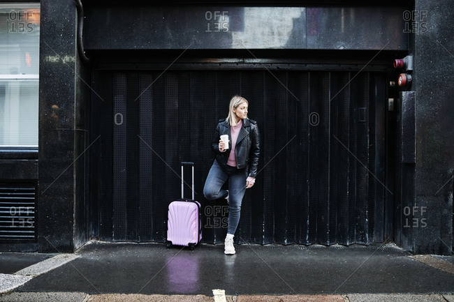 Young businesswoman walking with wheeled suitcase on city street. female in leather jacker walking with pink suitcase and holding a cup of coffee.