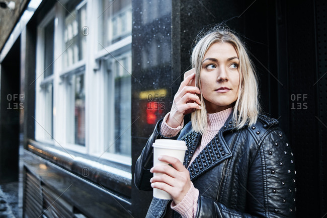 Pretty blonde woman stand on the street giving a phone call and drink coffee. businesswoman holding cup of coffee. winter.