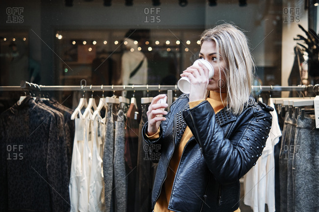 Portrait of young blonde woman wearing black leather jacket, drinking cup of coffee during shopping n front of shopping window with clothes behind.