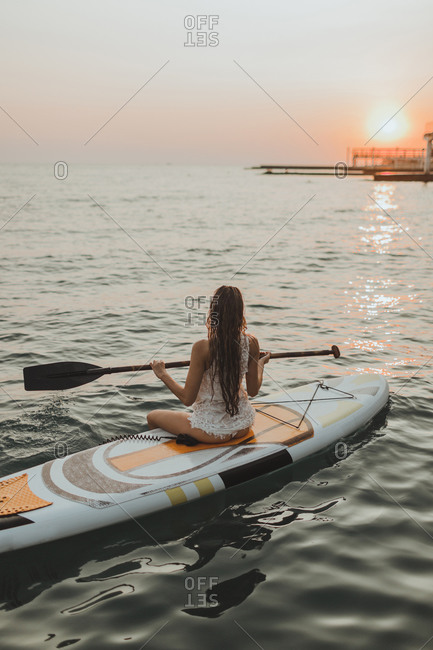 Young surfer girl sitting on a board with a paddle sunset