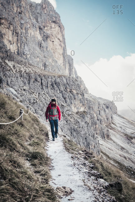 Young female hiking on trail next to steep mountain face in dolomites