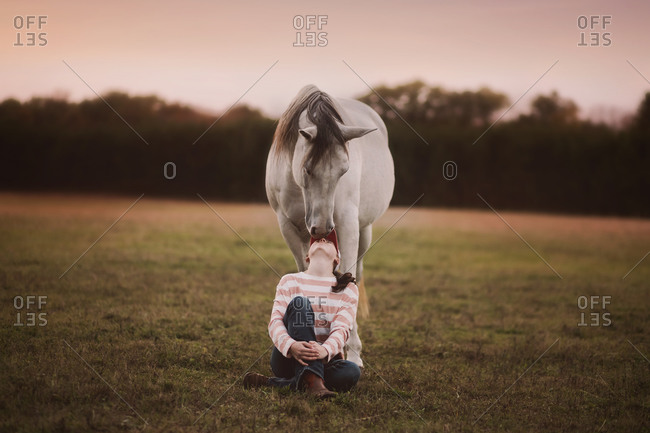 Teen girl sitting in front of horse affectionately looking up at horse
