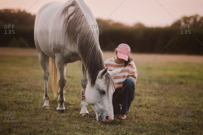 A woman in a pink hat touching a horse.