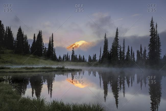 Mount rainier peeking through the clouds during early morning sunrise