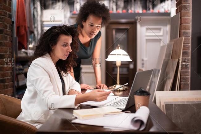 Smart multiethnic designers discussing blueprints on laptop