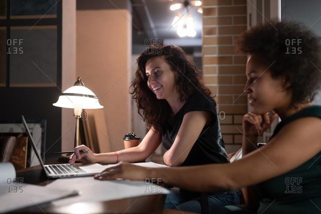 Happy diverse designers browsing laptop