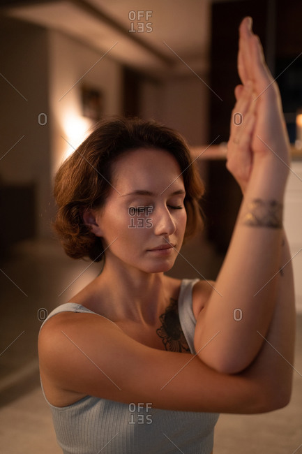 Young female meditating with eagle arms at night
