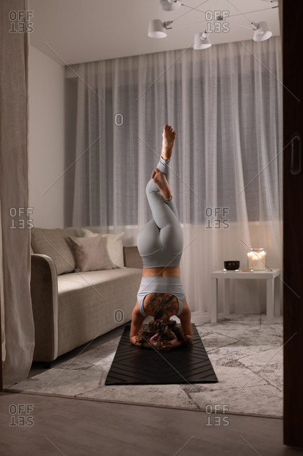 Unrecognizable woman doing eagle headstand