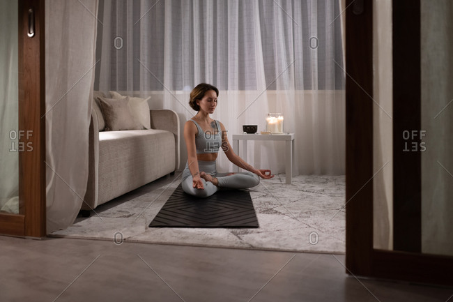 Young woman meditating in living room