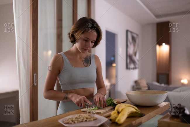 Young woman cooking healthy salad for dinner