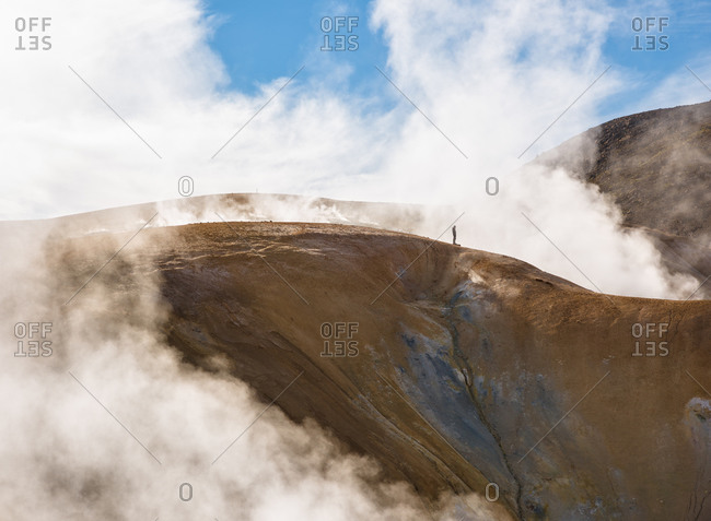 Lonely traveler on mountain range in clouds
