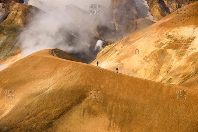 Hikers on mountain ridge on sunny day