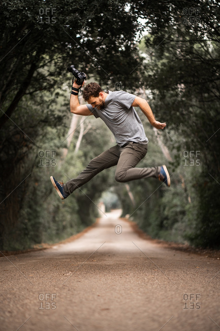 Young photographer jumps on a road where trees make a tunnel