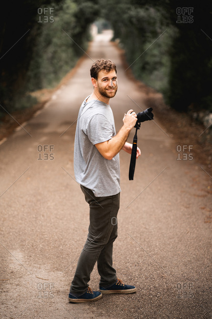 Photographer looks at camera on a road where trees make a tunnel