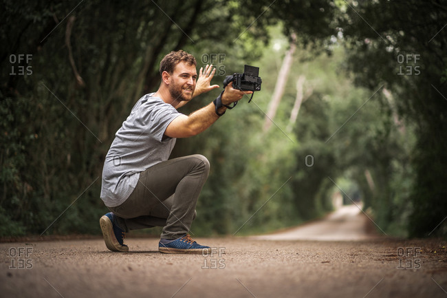 Smiling photographer takes selfie on a road where trees make a tunnel