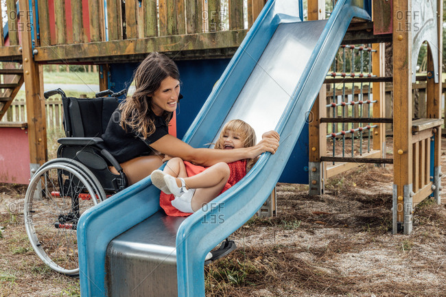 Little girl smiling and playing on a slide with her mother in a wheel chair