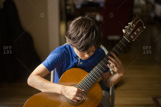 A boy hunches over a classical guitar playing a chord in window light
