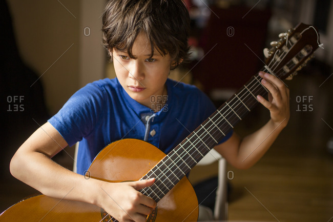 Close-up of a focused boy practicing classical guitar in window light
