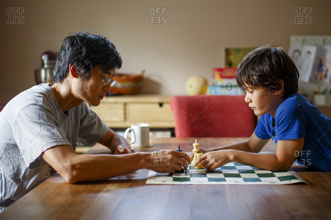A father and son sit together at a table playing a game of chess