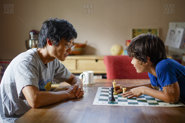 A boy makes chess move while playing with father at dining room table
