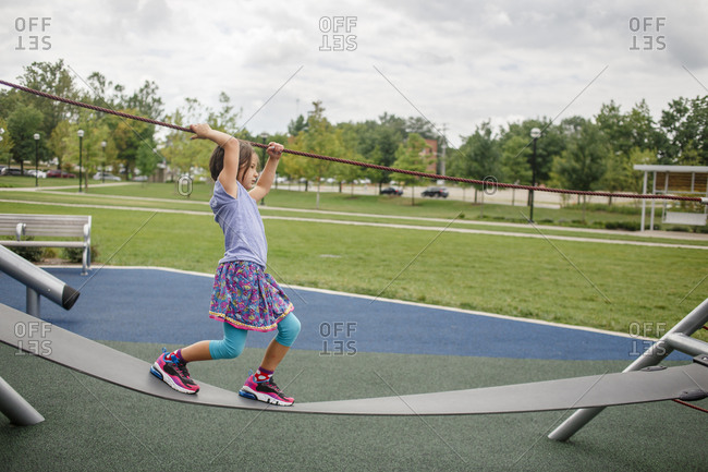 A little girl balances on playground equipment outside in summertime