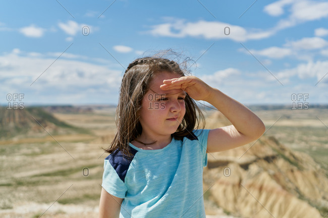 Girl wearing a blue blouse posing in the bardenas reales national park in navarra, spain. tourism concept