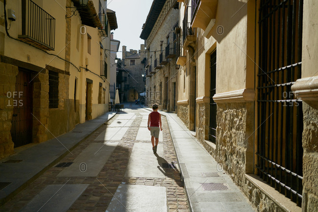 Young boy walking in an alley with old houses in rubielos de mora