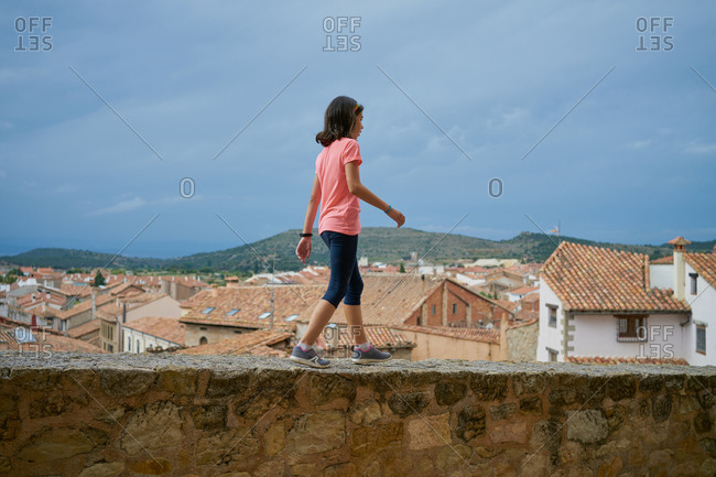 Young girl wearing a pink blouse walking on a stone wall with ho