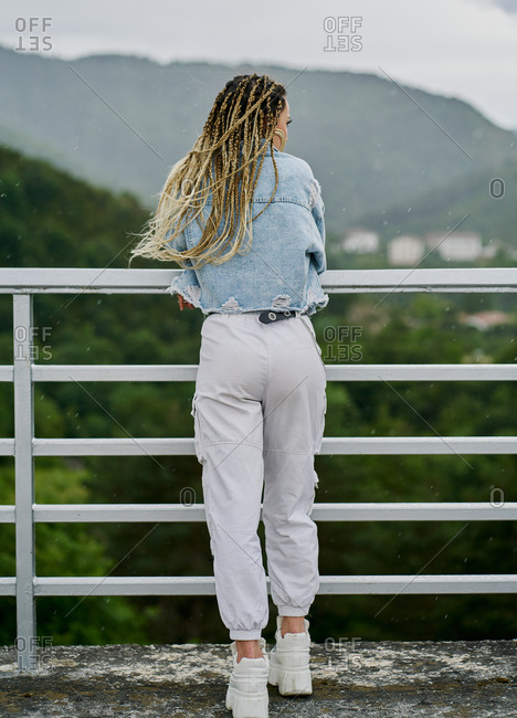 Back side of a young woman with blonde braided hair wearing a denim jacket and white jean resting on a dam