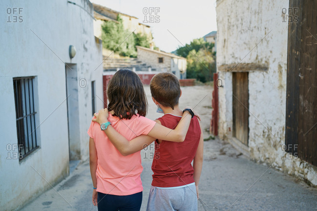 Back view of kids walking embraced along the street in a spanish village in teruel with a bullring in the background
