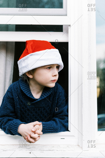Little boy looking out window waiting for santa clause on christmas
