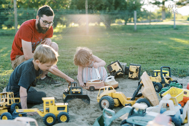 A father and his children playing in a sandbox with trucks together