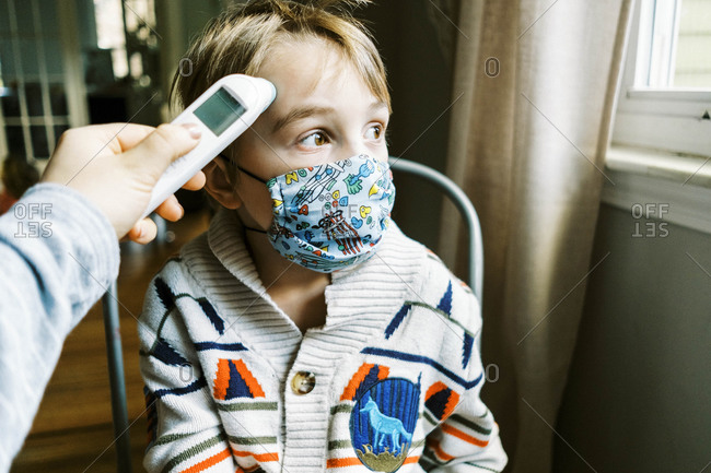 Child with fever wearing mask in home getting temperature taken