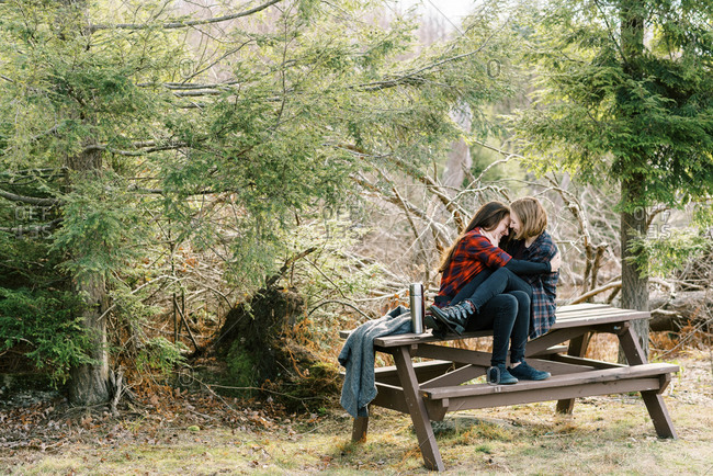 Cute gay couple sitting on bench after a hike and spending time together