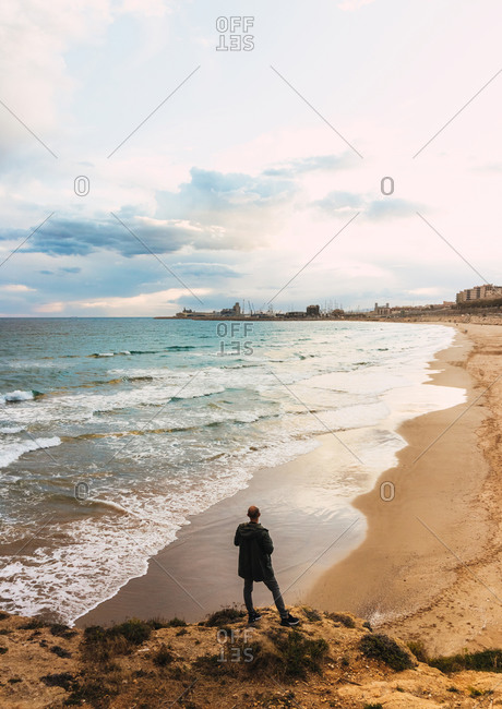 Views of a man from behind looking at a beach in a cloudy sky